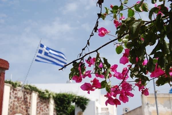 20_Ia-Oia-Santorin-Griechenland-Kykladen-Mittelmeer-griechische-Flagge-Blueten