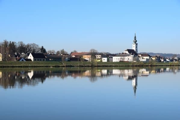 06_a-rosa-Flusskreuzfahrt-Donau-Spiegelung-Ortschaft-Kirche-Oesterreich